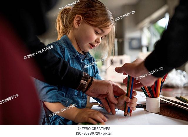 Man showing daughter drawing with handful of coloured pencils at table