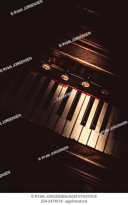Dark still life details on the keys of a piano in the shadows of darkness. The vintage music hall