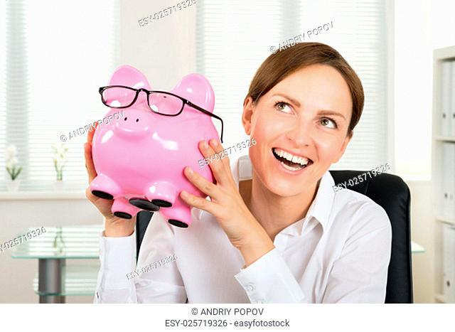 Portrait Of Happy Businesswoman Holding Piggybank With Eyeglasses In Office