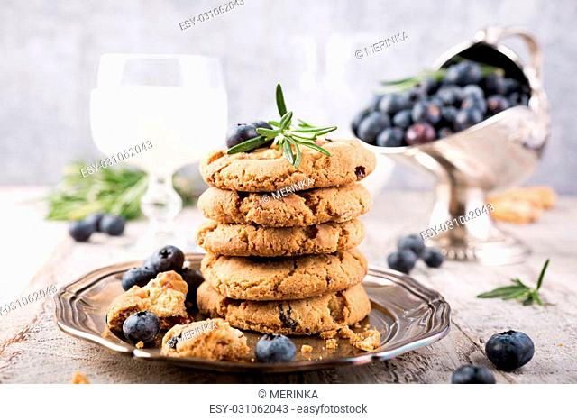 Stack of chocolate chip and blueberries cookies on metal plate with glass of milk decorated with rosemary sprigs. Selective focus