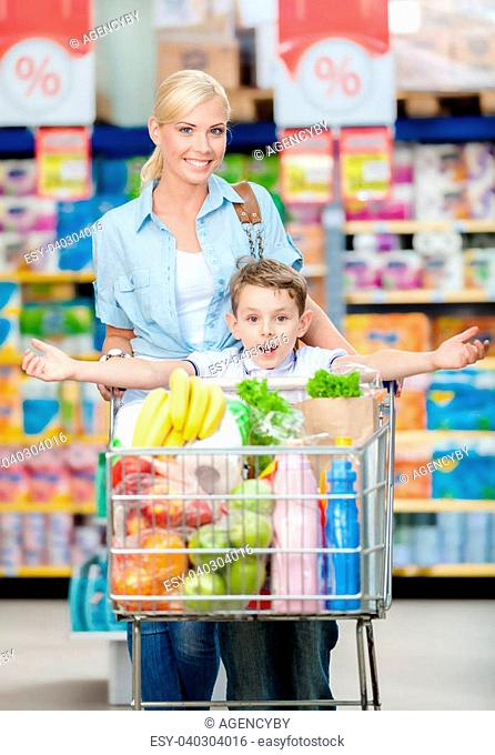 Mother and son whose arms are outstretched keeps cart full of products in shop. Concept of healthy food and consumerism