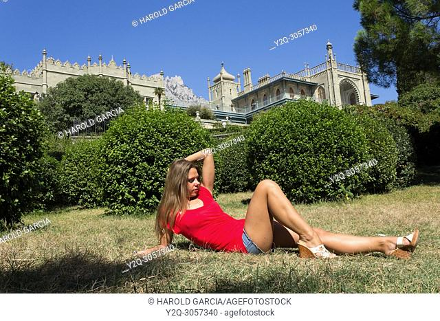 Beautiful woman posing in shorts and small shirt for the camera near the Vorontsov Palace in Alupka, Crimea