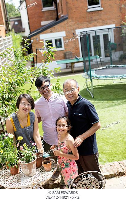 Portrait smiling multi-generation family gardening, potting flowers in sunny yard