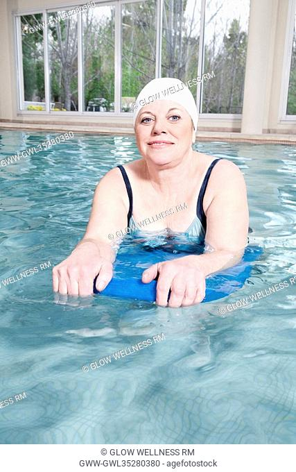 Portrait of a woman swimming with a float in a swimming pool