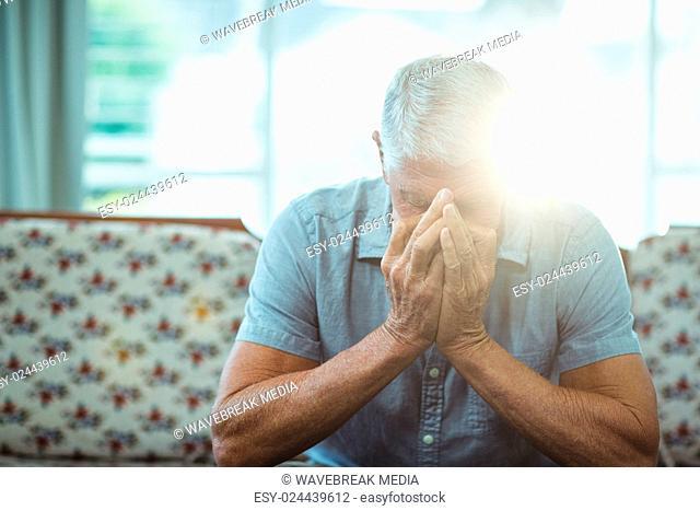 Worried senior man sitting in living room