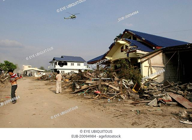 Tsunami. Locals look up at a helicopter which is surveying the damage caused by the tsunami, nothing is left standing in the village 2500 people are pressumed...