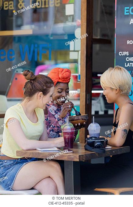 Young women friends drinking smoothies and eating at sidewalk cafe