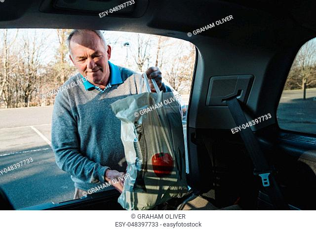 Senior man is placing shopping bags in the boot of his car