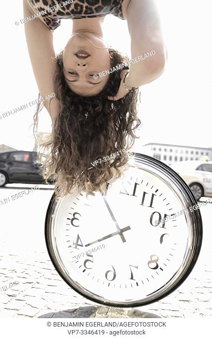 young emotional woman upside down with clock at street in city Berlin, Germany