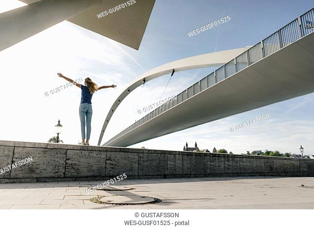 Netherlands, Maastricht, young woman standing on a wall at a bridge