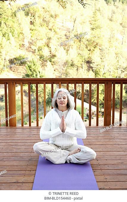 Older Caucasian woman meditating on wooden deck