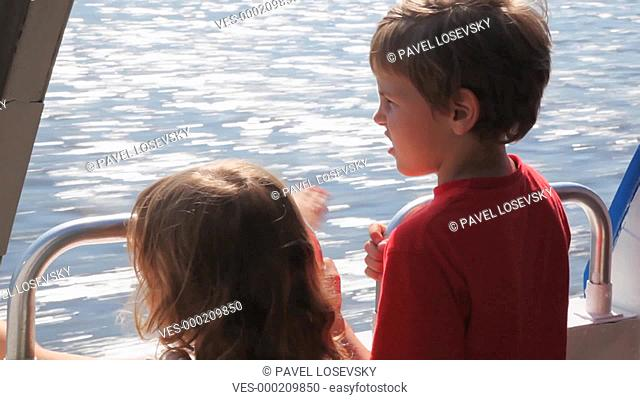 boy and his little sister float fast moving boat hydrofoil on sea in day summer, closeup