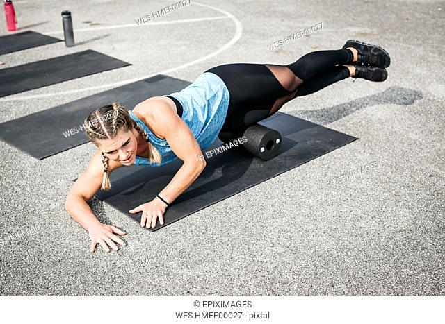 Woman doing workout exercise with fascia roll outdoors