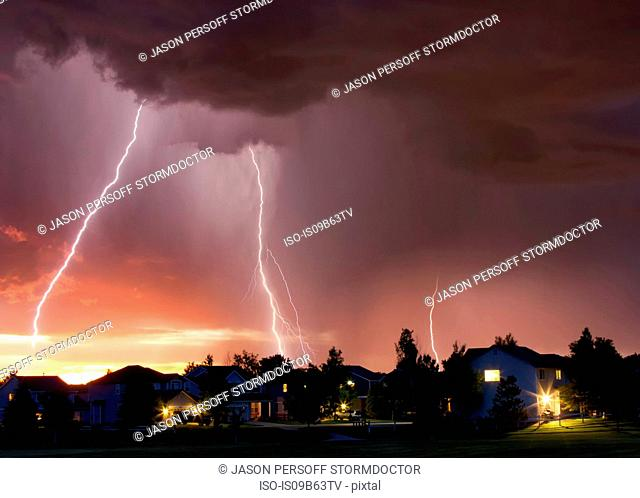 Forked lightning in orange sky over urban area, Aurora, Colorado, United States, North America