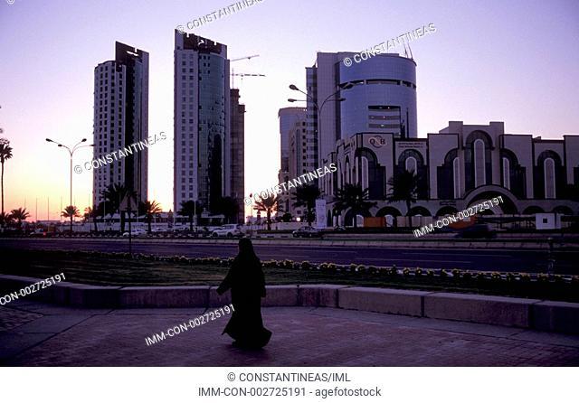 Woman walking along the Corniche pedestrian street, Doha, Qatar, Middle East