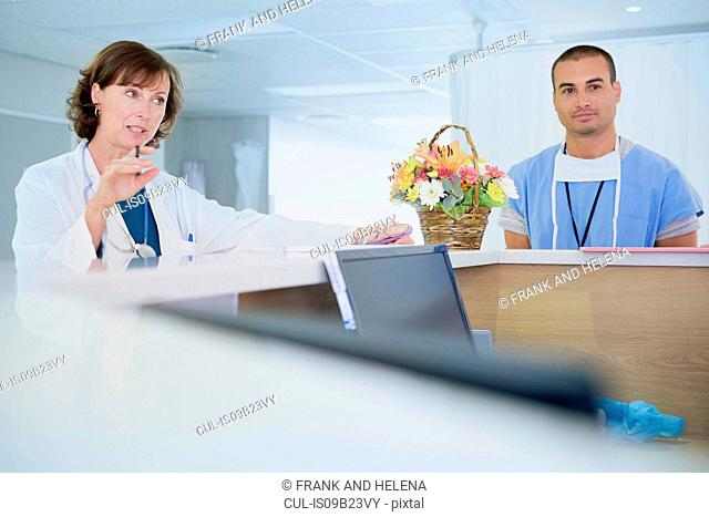 Female doctor talking at nurses station in hospital