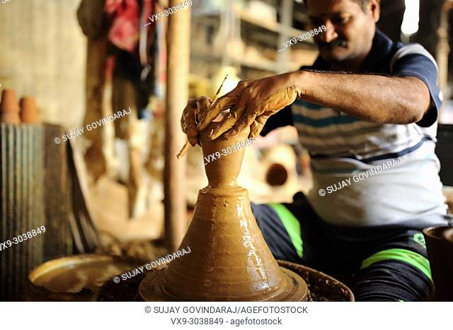 Bangalore, India - October 15, 2016: Unknown potter making earthen ware from fresh clay at his work site in the Pottery Street, Bangalore, India