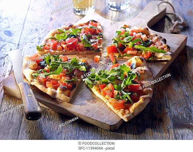 Pizza bread with tomatoes and rocket, sliced on a wooden board