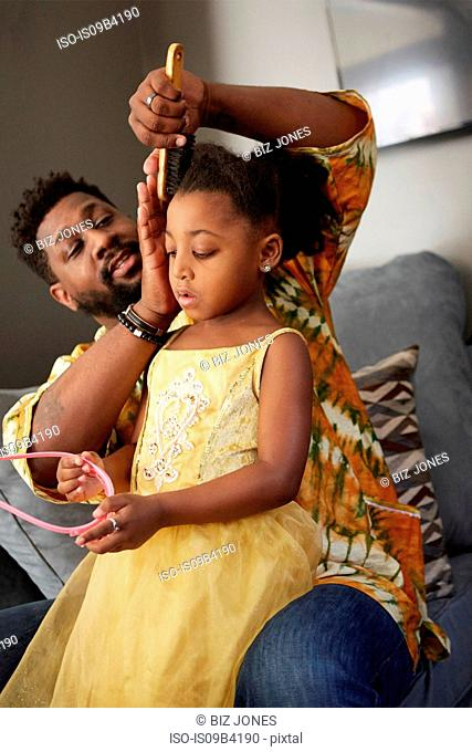 Man on sofa brushing daughter's hair for princess tiara