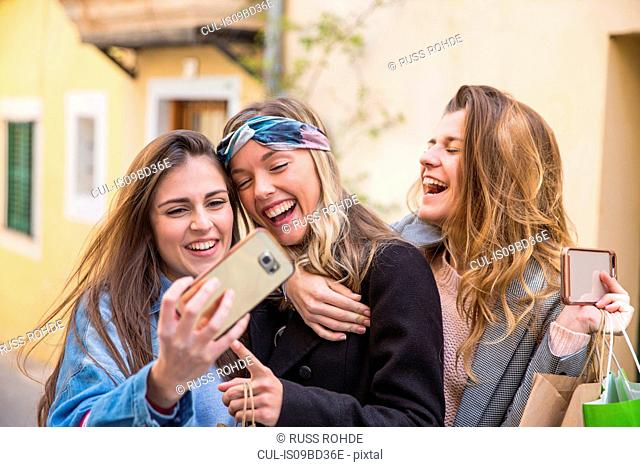 Friends taking selfie in street