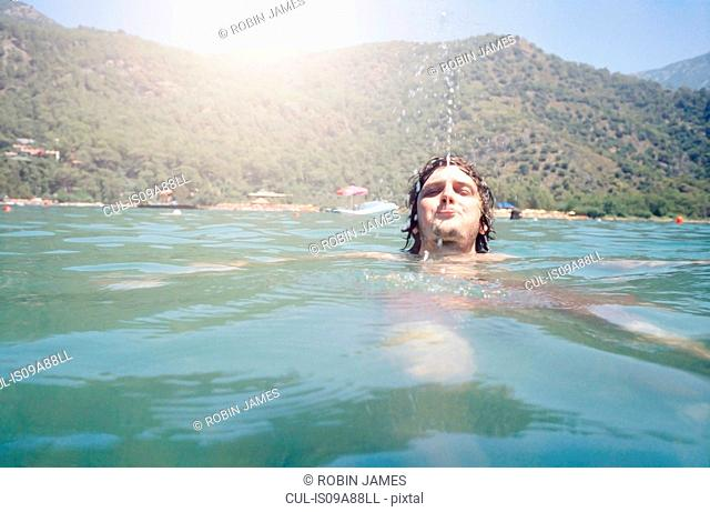 Man swimming and blowing water from mouth