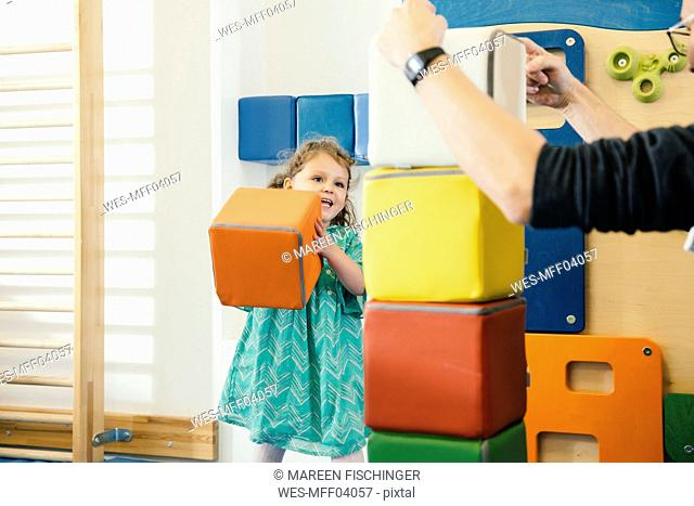 Happy little girl lifting up a soft building block in gym room of a kindergarten