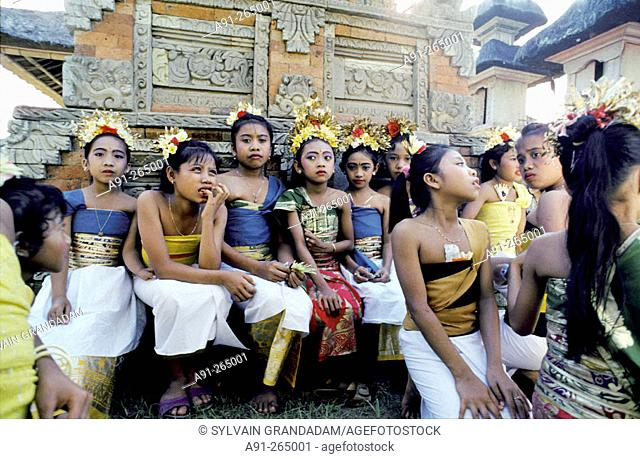 Children in festival dresses waiting for the procession starts. The Great Odalan for Singapadu Temple. Bali Island. Indonesia