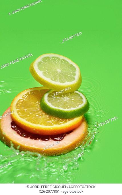 Citrus fruits, grapefruit, orange, lemon and lime slices splashing in water on green background