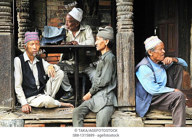 There are many old people sitting by the street in the old town