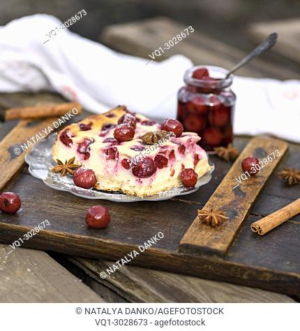 cheesecake with berries of cherries in a glass plate and a jar of berries
