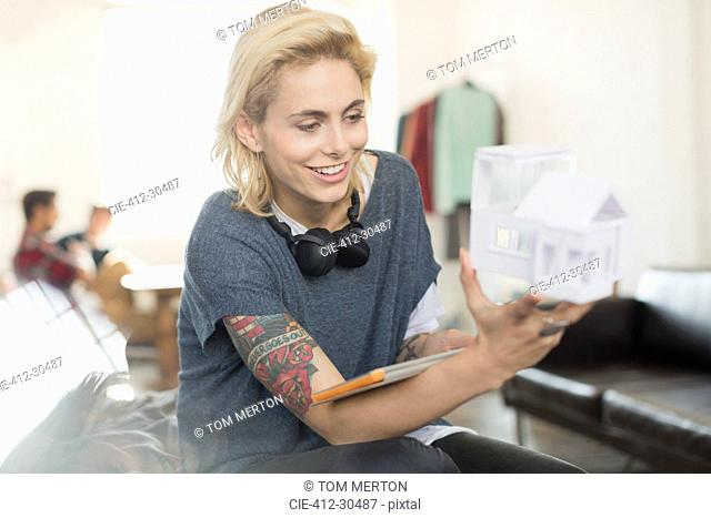 Smiling young tattooed female architect holding model