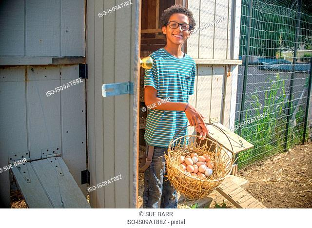Portrait of boy in hen house with basket of eggs