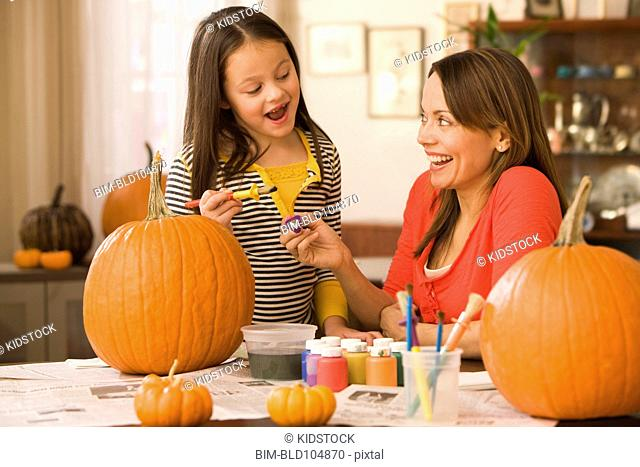 Caucasian mother and daughter decorating pumpkins