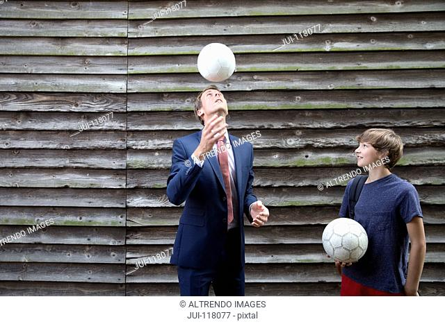 Businessman Father Playing Soccer With Teenage Son