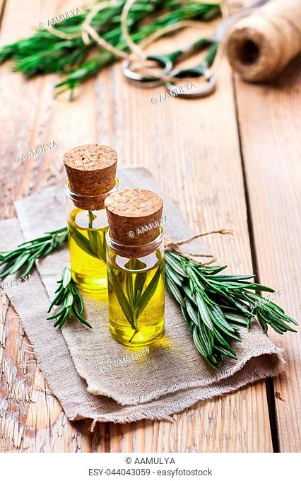 Healthy lifestyle concept. Natural rosemary essential oil on a rustic wooden table for beauty, spa, therapy. Selective focus