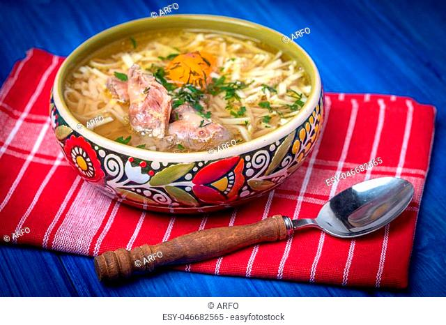Soup with noodles and chicken in a ceramic bowl