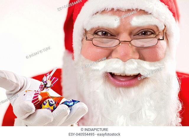 Close-up of happy Santa Claus offering chocolates