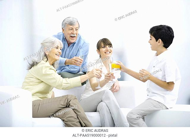 Multi-generation family clinking glasses, smiling at each other