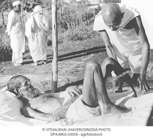 Mahatma Gandhi giving massage to a leper patient at Sevagram Ashram, 1940