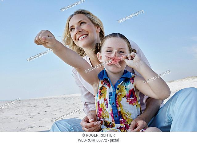 Happy mother with daughter on the beach