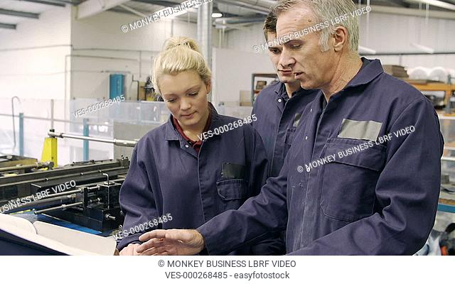 Engineer explaining to male and female apprentices how to operate hydraulic pipe bending machine.Shot on Sony FS700 in PAL format at a frame rate of 25fps