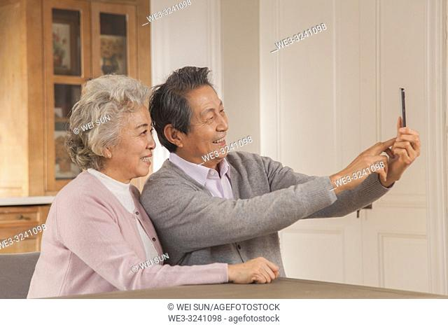 Happy old couple take selfies with their cell phones, Chinese ethnicity