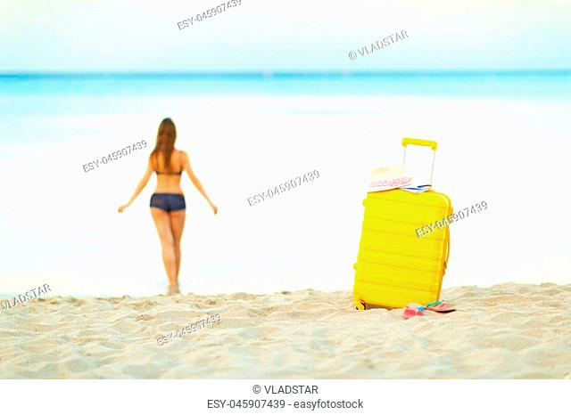 Bright yellow suitcase on the beach and a girl walks into the sea in the background