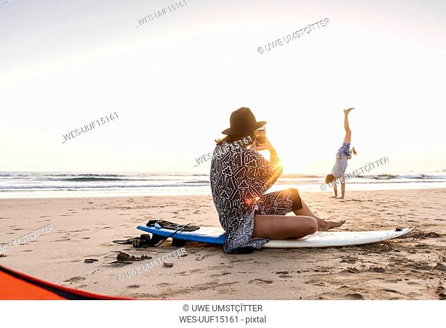 Young woman sitting on surfboard, taking pictures of young man, practicing handstands on the beach