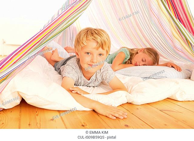 Portrait of boy and sister lying in bedroom tent