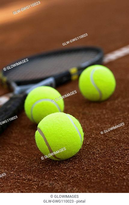 Close-up of three tennis balls and a racket in a court