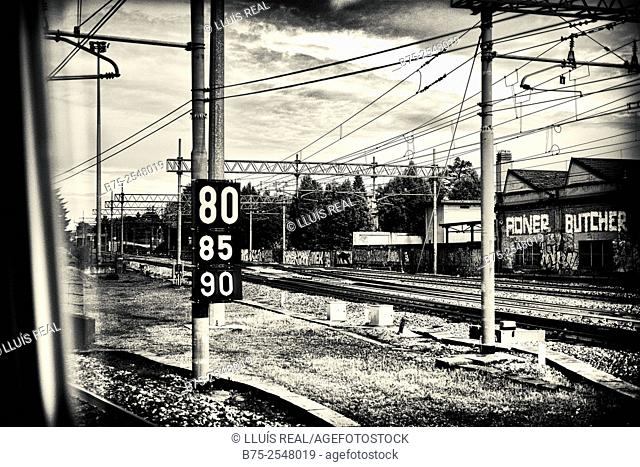 View from a train window, of the industrial area with industrial buildings, rail tracks and wires and a sign post with numbers, 80, 85, y 90