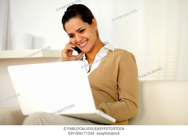 Portrait of a charming young female speaking on cellphone in front of her laptop at home indoor