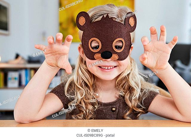 Portrait of young girl wearing bear mask