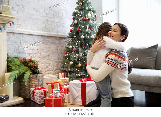 Mother and daughter hugging near Christmas tree and gifts in living room